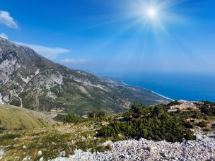 Summer  Llogara pass sunshiny view  with road, herd of goats on slope and sea water surface (Albania)